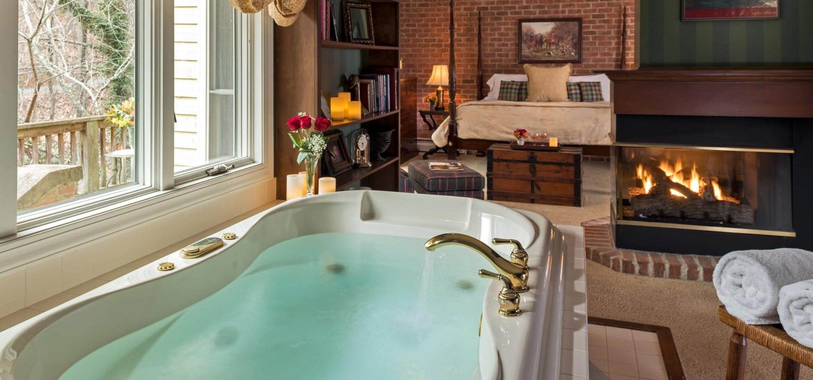 Carriage House Suite Jacuzzi bath, fireplace, and bed