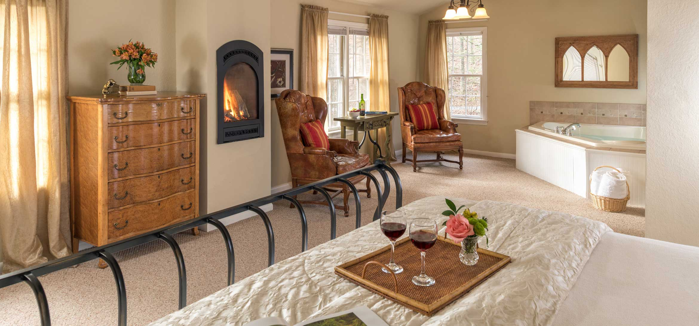 Sunrise Suite bed, sitting area, fireplace, and jetted tub
