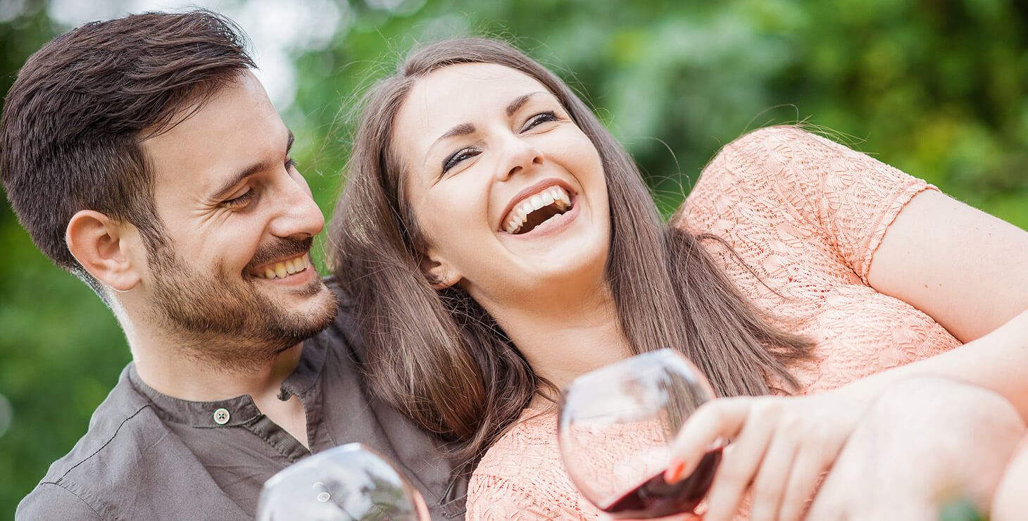 Couple laughing together while drinking wine