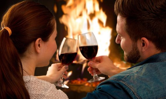 Couple drinking wine and relaxing by a fireplace