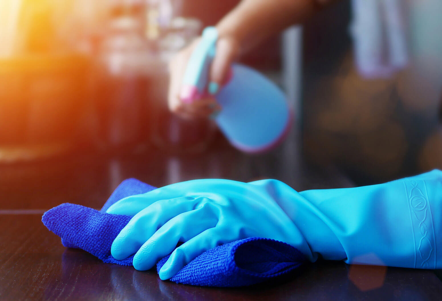 gloved hand wiping down a counter